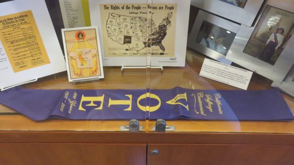A purple banner posed in front of several photographs