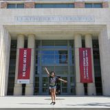 A young woman poses with one arm out and the other up in front of the main entrance to the Leatherby Libraries