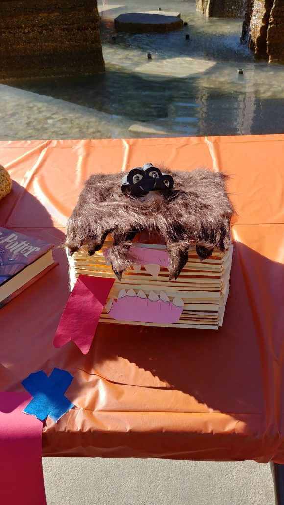 A plastic pumpkin decorated as the Monster Book of Monsters, using paper and fake fur