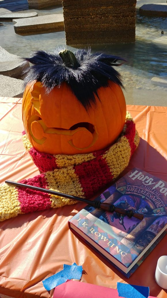A pumpkin carved to resemble Harry Potter, with the silhouette of the character's glasses and scar, with black fake hair on top, and a red and gold scarf wrapped around the bottom, with a wand and copy of the first Harry Potter book displayed near it.