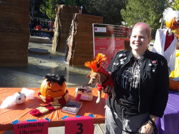 A woman and a dog, both dressed like punk rockers, stand next to the table with the decorated pumpkins