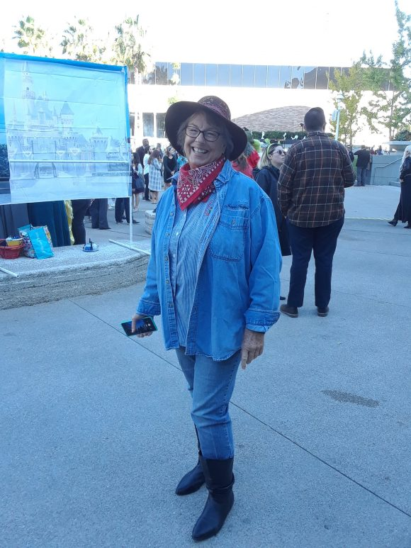 A woman wearing a cowgirl costume stands posing