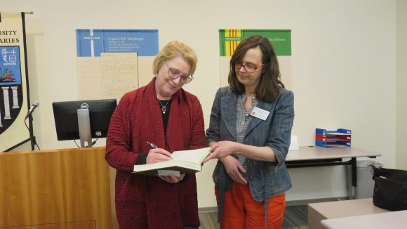 Two women stand next to each other; the woman on the left signs a book while the woman on the right holds the book open and looks on.