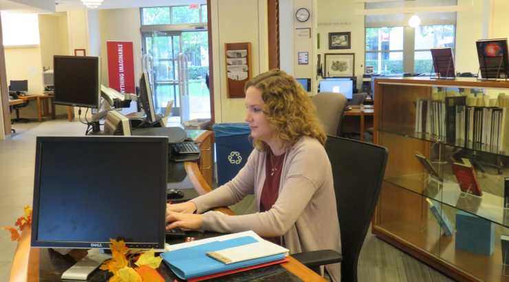 Lauren Dubell sitting at the Reference Desk, typing on the computer