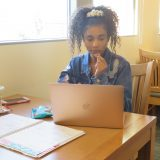 Ruby sits behind her laptop at a study carrel, munching on cookies while studying