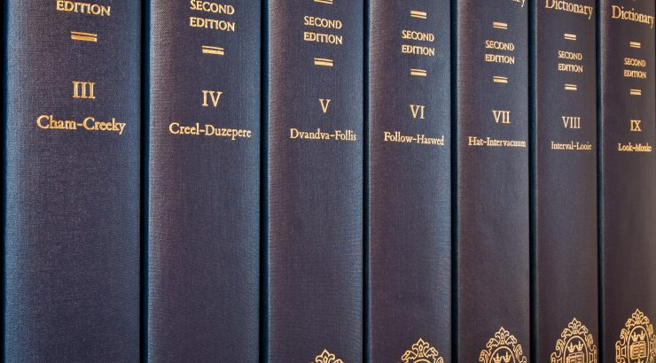 Close-up photograph of the spines of several print volumes of the OED