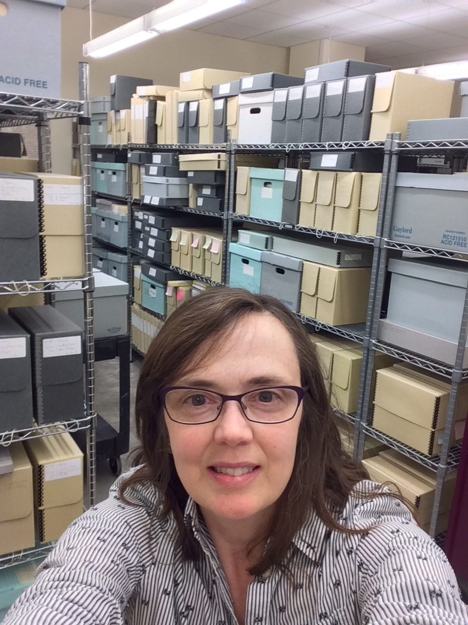 A selfie of Wendy Gonaver from the neck up, with archive boxes behind her