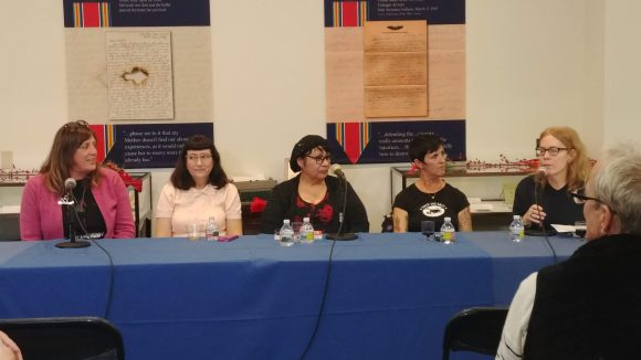 Five women sit at a table covered in a blue tablecloth, with microphones in front of them