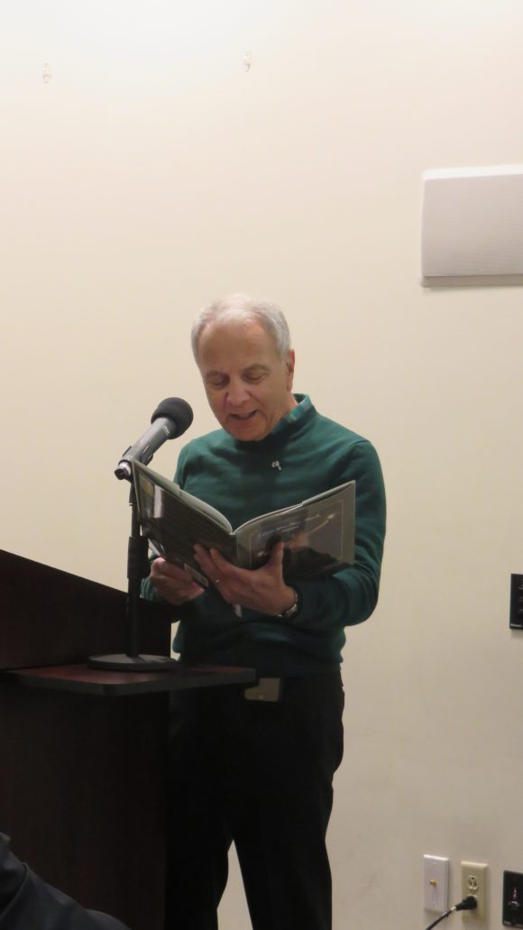 A man stands behind a lectern holding open and reading from a large picture book