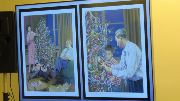 A projector screen showing two side-by-side illustrations of a family decorating a Christmas tree
