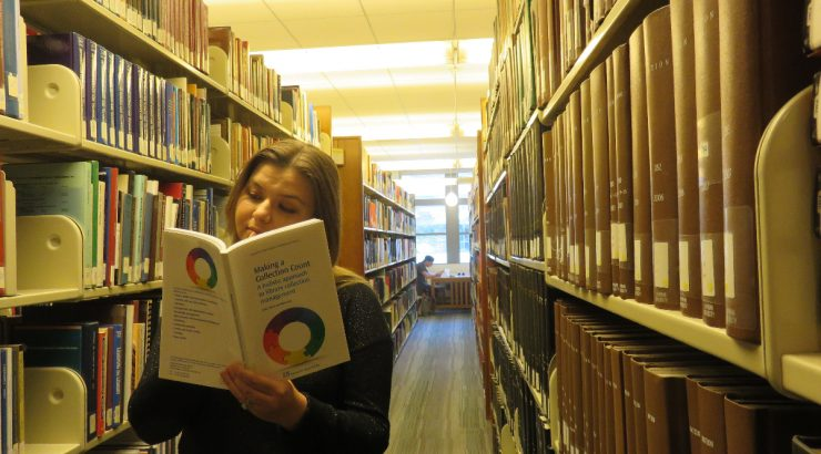 Kristin stands among shelves of books, reading an open book called Making a Collection Count