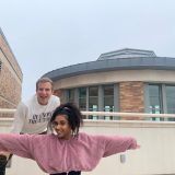 Ruby Blakesleay, in a pink sweater, poses in front of Jimmy Elinski, on a patio of the Leatherby Libraries