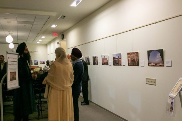 Guests with their backs turned to the camera stand next to photos displayed on the wall to the right of the frame