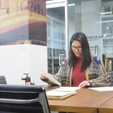 Archivist Tiana Taliep sits reading papers at a table. A glass door behind her is the entrance to the Oskar Schindler Archives.