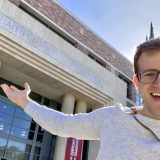 Jimmy Elinski stands smiling for the camera pointing at the entrance to the Leatherby Libraries behind him