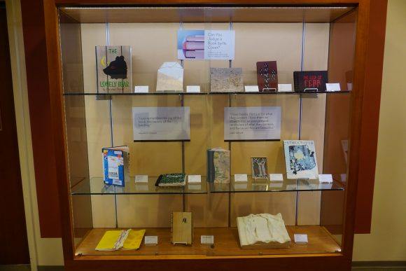 A display case with three glass shelves, each containing a number of artists' books.