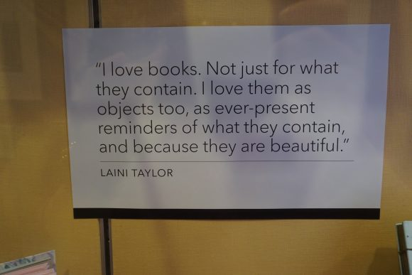 """A piece of paper in a display, with text that reads """"I love books. Not just for what they contain. I love them as objects, too, as ever-present reminders of what they contain, and because they are beautiful. - Laini Taylor."""""""
