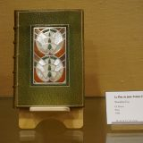 Close-up of a book with a detailed green cover with inlaid mother-of-pearl designs