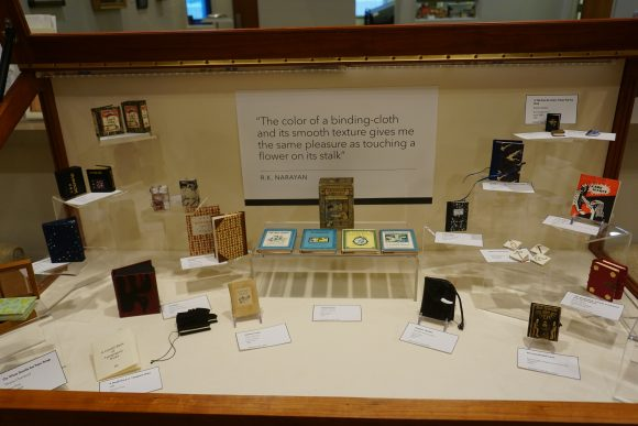 A horizontal display case containing a variety of miniature books