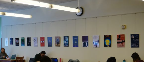 "Book covers, printed as 11"" x 17"" posters, hanging on the wall above studying students."