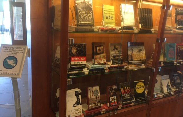 A wood and glass display case containing approximately 20 books, all on the topic of war