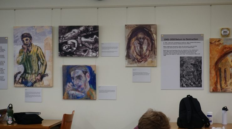 Paintings and explanatory text hanging on a wall over desks where students are studying.