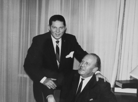 Black and white photograph of two men in suits, one seated and one standing behind him with a hand on the seated man's shoulder