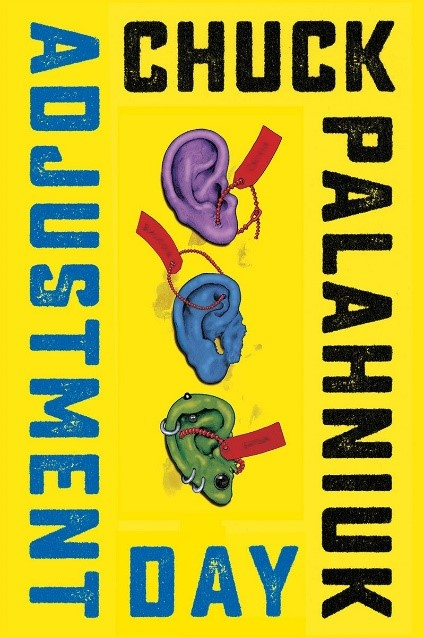 Cover of Adjustment Day by Chuck Palahnuik. Cover has a yellow background. The title is in blue font on the left hand and bottom sides of the cover, and the author's name is in black font on the top and right hand sides of the cover. In the center are three ears in a vertical row, in purple, blue, and green, from top to bottom, with red tags attached to each one.