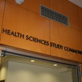 Photograph of the outside of the Health Sciences Study Commons, showing those words on a wooden wall over an open door