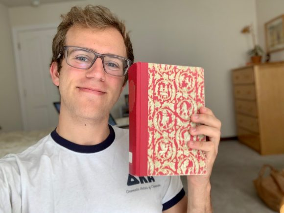 A young blonde man wearing glasses and a white and blue t-shirt holds up a red and yellow patterned hardback book
