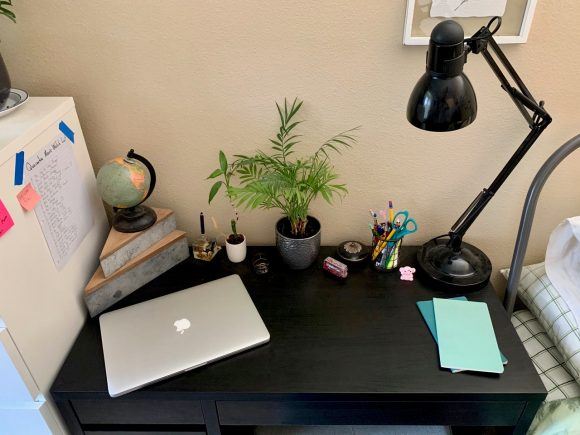 A black desk, with a silver Apple laptop, a mini globe, three small plants, a black lamp, a few desk tools, and two bright blue pieces of paper on it