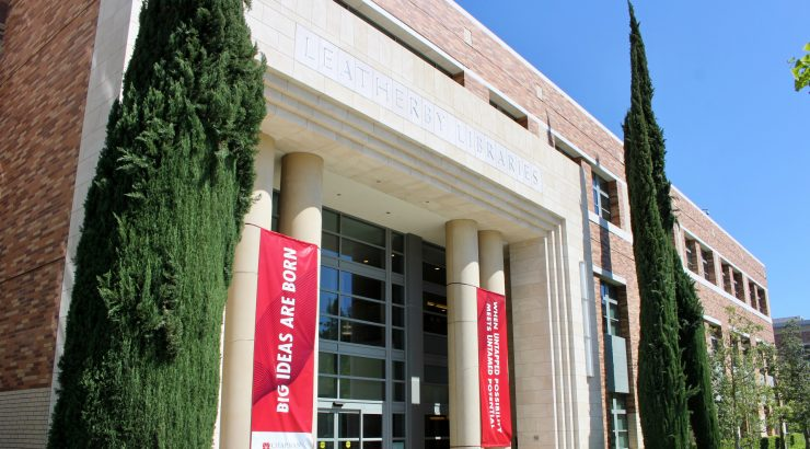 Exterior photograph of the Leatherby Libraries, taken from a low angle on the Wells Fargo stage outside the front of the library