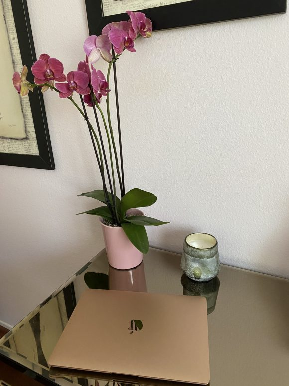 A rose gold Apple laptop sitting on a glass-top table, with a candle and a potted pink orchid behind it,