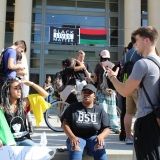Photograph of the exterior of the Leatherby Libraries. A Black Lives Matter banner, along with a red, black, and green flag, is hanging over the door. Students sit and stand in front of the door, including two Black female students sitting talking to a standing White male student