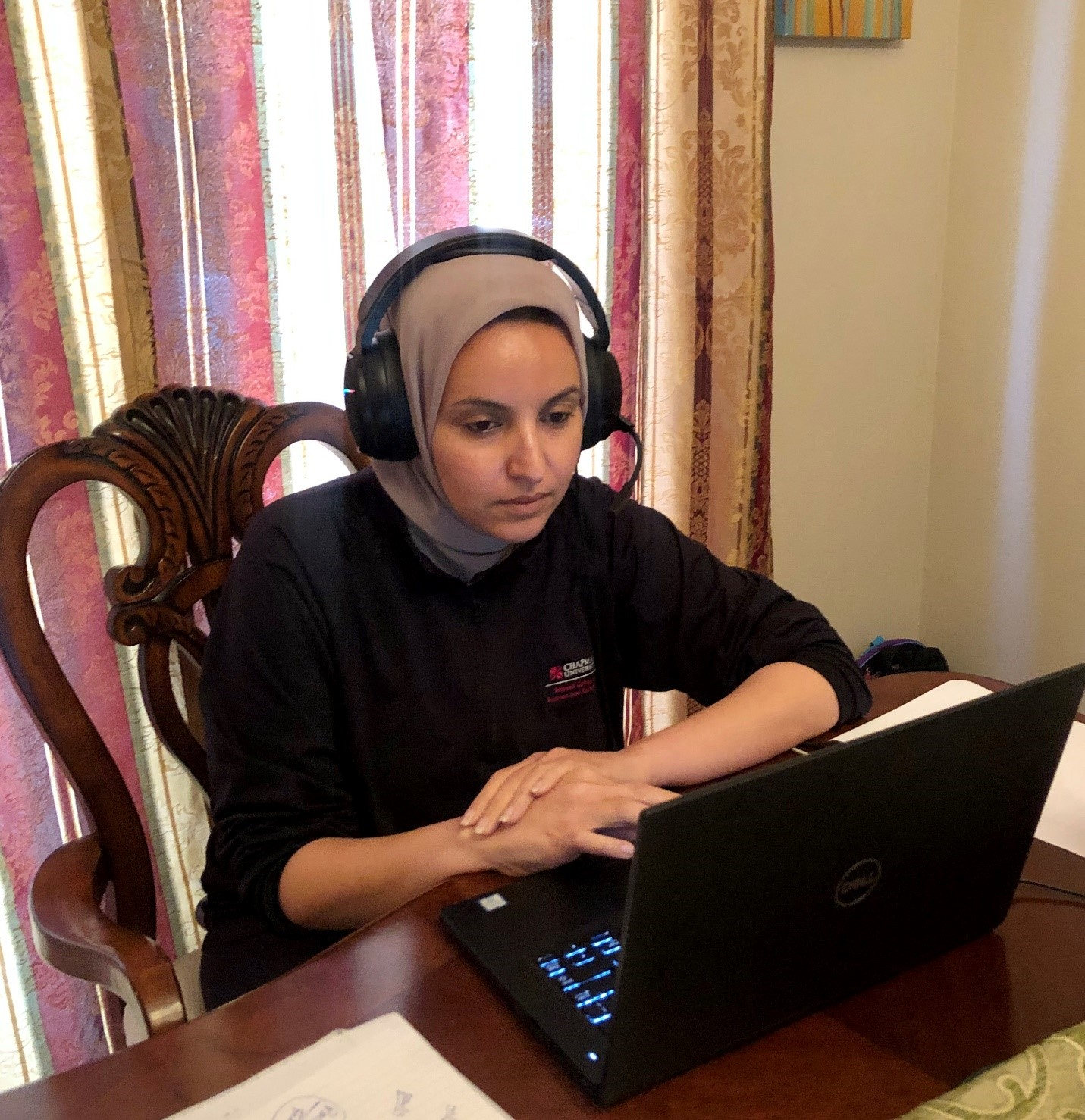 A woman wearing a headscarf and large over ear headphones sits at a table working on a laptop.