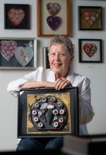 Portrait of Slater Barron posing with some of her framed lint sushi artwork, with more of her framed artwork on the wall behind her