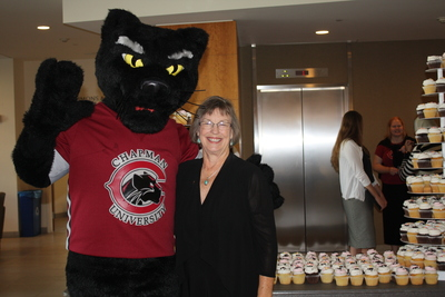 A person in a Pete the Panther mascot costume and a red Chapman University t-shirt poses with Dean Baldwin, who is wearing a black blouse, in front of a table filled with cupcakes, set in front of the elevator bay.