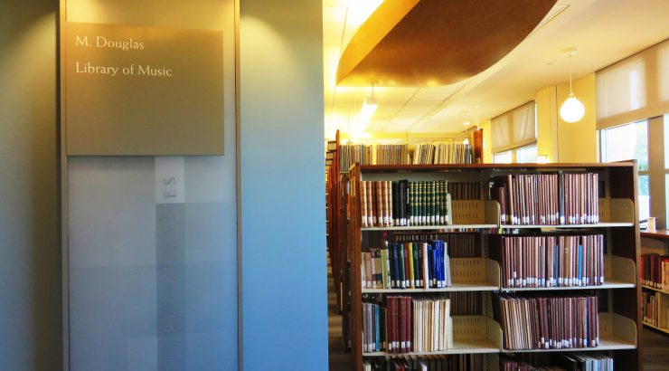 Photograph of the M. Douglas Library of Music in the Leatherby Libraries. A pillar with a sign bearing the name of the library is on the left, and bookshelves filled with books are in the background on the right