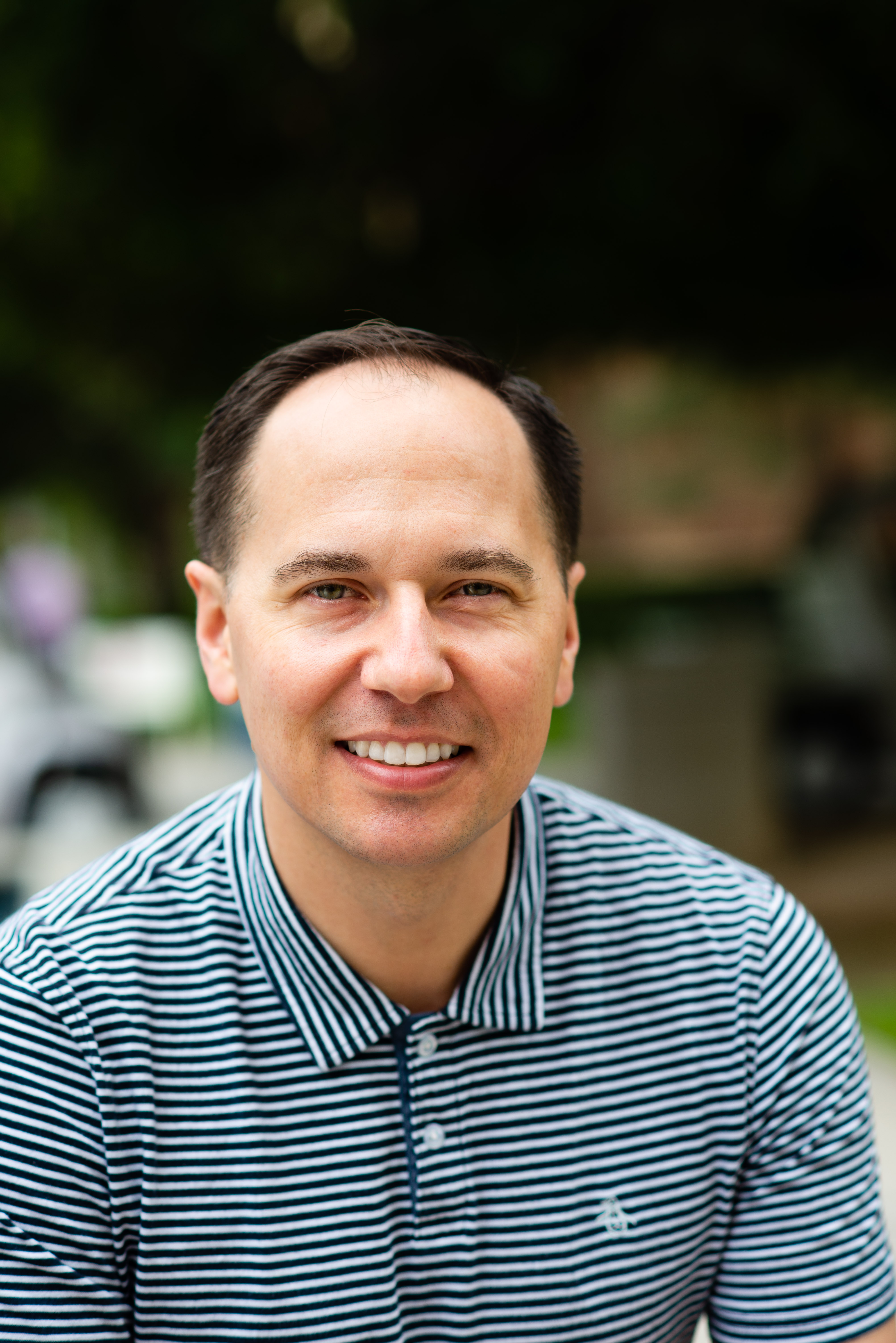 Headshot of a white man in a blue striped polo shirt