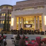 Exterior of the Leatherby Libraries at dusk with an orchestra playing on the stage, a Homecoming banner across the doors, and audience members seated at tables in the Attallah Piazza.