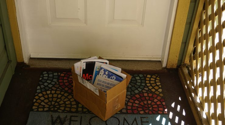 A cardboard box with library books standing up inside it sits on a Welcome mat in front of a door.