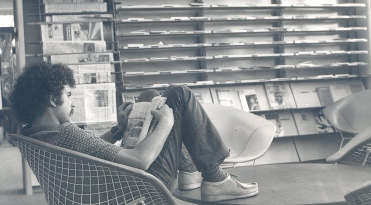 Black and white picture of a male student reading a book in the Thurmond Clarke Memorial Library