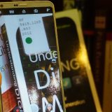 Close-up of a hand holding a cell phone, which is open to the camera feature and zoomed in on the library call number sticker on a book on a bookshelf.