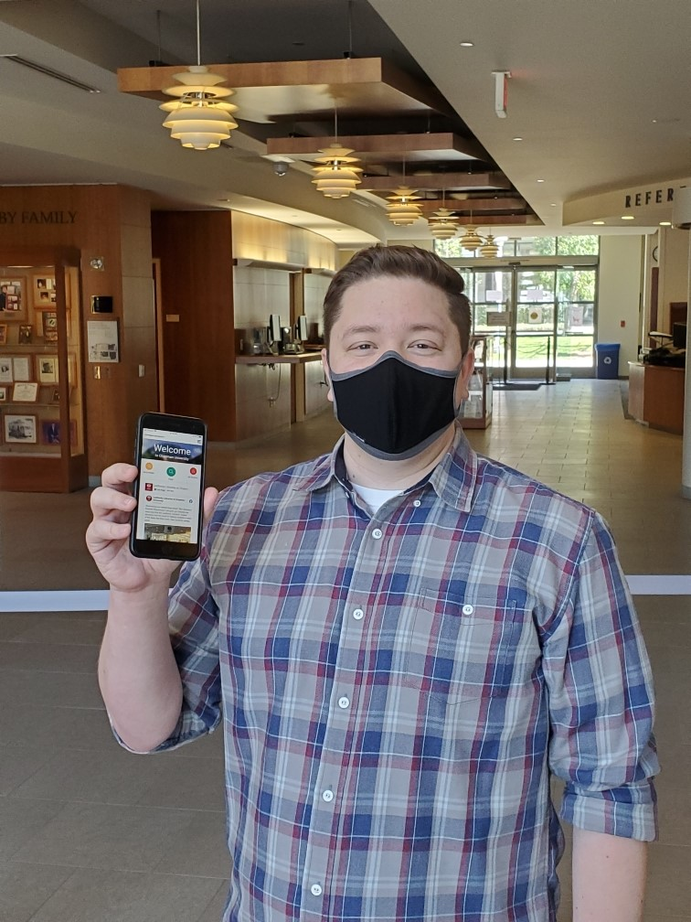 A man in a mask holding up a cell phone