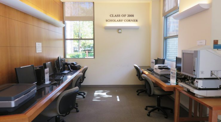 Class of 2008 Scholars Corner in the Leatherby Libraries. Two rows of counter-top desks with computers and chairs on either side of an aisle, with a wall at the far end