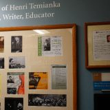 """A framed collage on a blue wall under white vinyl lettering that reads, """"The Legacy of Henri Temianka Musician, Writer, Educator"""""""