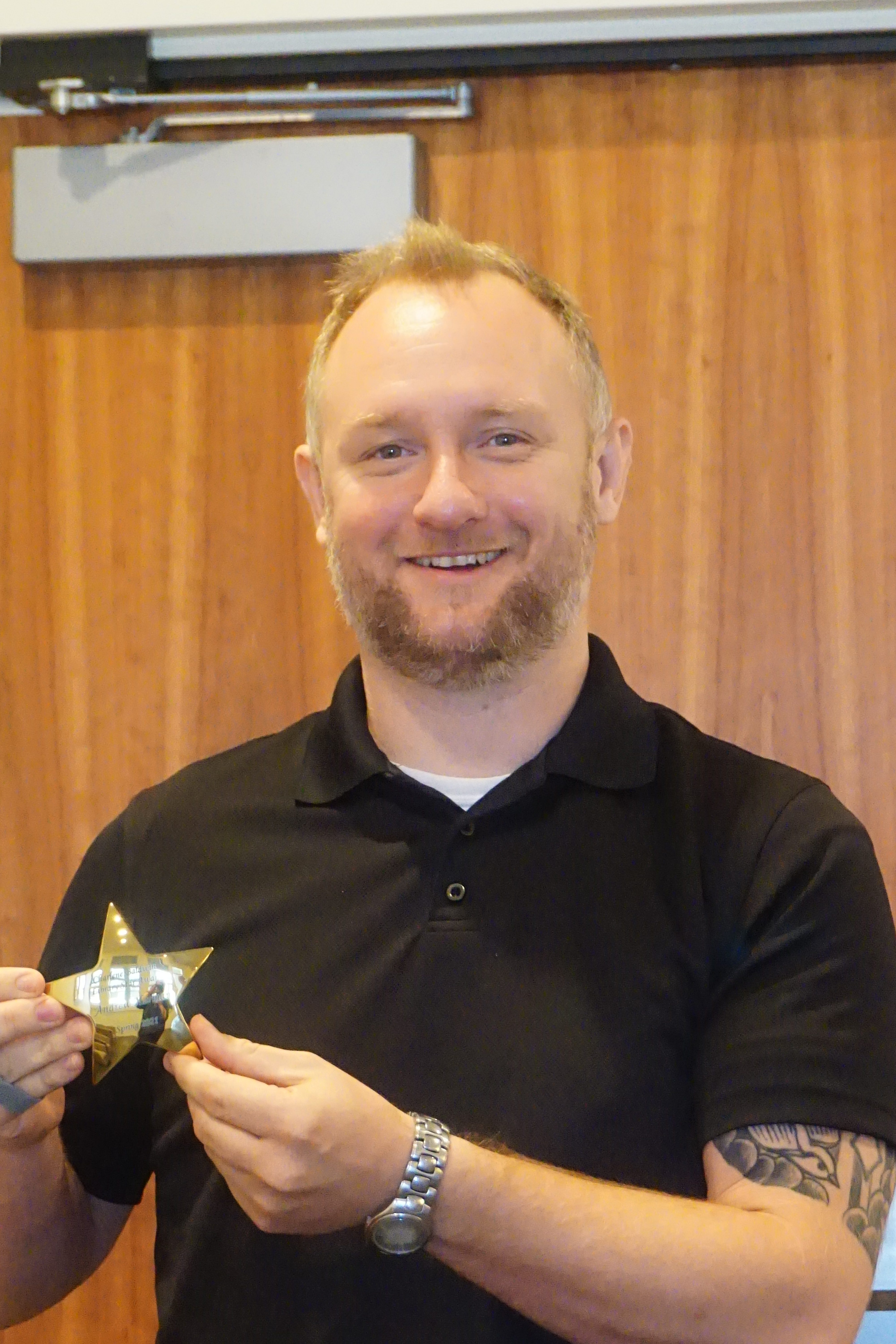 A man smiling for the camera and holding up a small gold star.