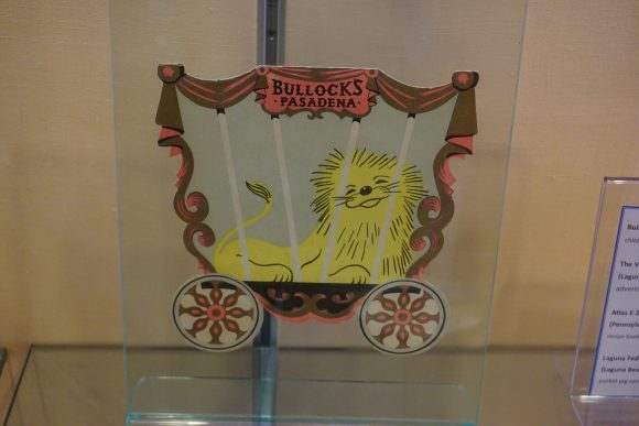 A die-cut children's menu in the shape of a wagon, with an illustration of a lion inside the wagon.