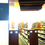 """Rows of bookshelves covered in books. In the foreground is a wall with a sign that reads """"Doy and Dee Henley Library of Social Sciences"""""""