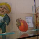 Several die-cut paper objects (a figure of a man yelling, an orange, and a covered wagon) on a glass display shelf.